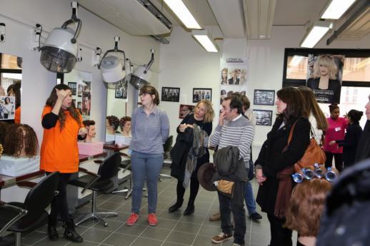 Une élève de l'atelier coiffure donne des explications aux visiteurs.